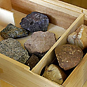 A box full of stones from the Kreydenweiss family vineyards in Alsace: Dark-gray granite, pale-tan schist, reddish sandstone.